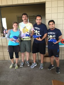 The Random Meta ChGs, the winning team of the 13th annual Adventure Race, pose at Lake Claire's pavilion with their prize packages in hand. Left to right: Laura Sisken, Colin Constant, Abraham Vazquez, and Rafael Guzman. Photo credit: Lauren Pierce