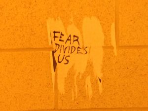 UCF College Democrats officer Peter Yañez wrote 'Fear Divides Us.' messages over the white patches left behind by removed white nationalist fliers. Photo by: Cristóbal Reyes